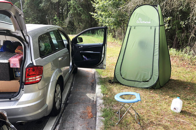 Associated Press editor Michael Warren's car sits next to a fold-out toilet seat and a pop-up changing tent at a rest area along Interstate 75 in Florida on July 25, 2020. Warren considers these two items essential to long-distance road trips in the pandemic. (AP Photo/Michael Warren)