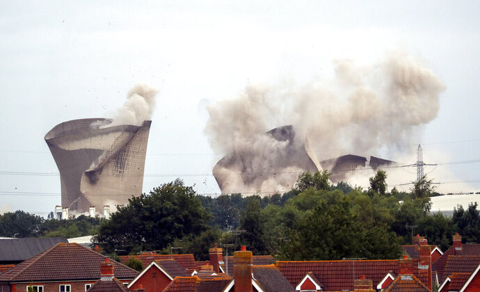 The cooling towers at the disused coal-fired Didcot power station in Oxfordshire, England are demolished Sunday Aug. 18, 2019. Demolition work began on the remains of the coal-fired power station where four workers were killed when it collapsed several years ago. (Steve Parsons/PA via AP)