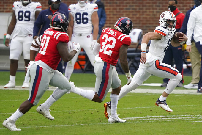 Auburn quarterback Bo Nix (10) is pursued by Mississippi linebacker Jacquez Jones (32) and defensive tackle Hal Northern (91) during the first half of an NCAA college football game in Oxford, Miss., Saturday Oct. 24, 2020. (AP Photo/Rogelio V. Solis)