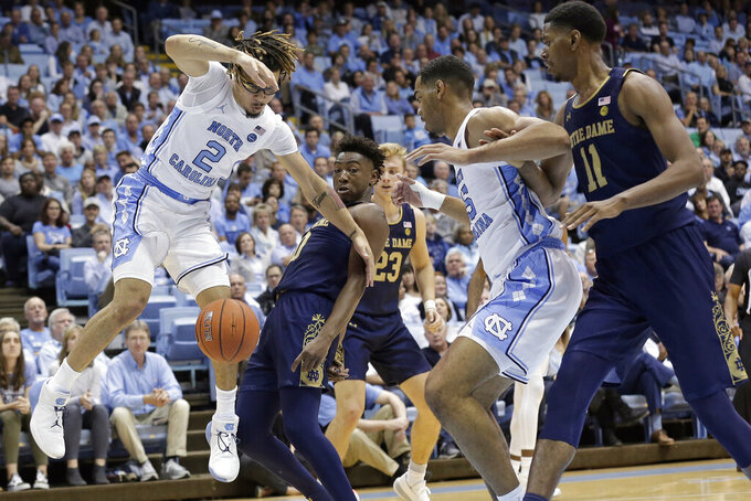 Notre Dame guard TJ Gibbs guards North Carolina guard Cole Anthony (2) while North Carolina forward Garrison Brooks (15) and Notre Dame forward Juwan Durham (11) look on during the first half of an NCAA college basketball game in Chapel Hill, N.C., Wednesday, Nov. 6, 2019. (AP Photo/Gerry Broome)