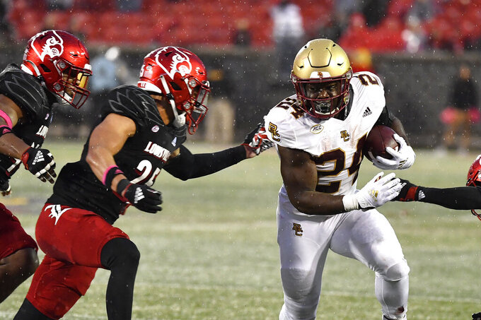Boston College running back Pat Garwo III (24) attempts to get away from Louisville defensive back Josh Minkins (25) during the second half of an NCAA college football game in Louisville, Ky., Saturday, Oct. 23, 2021. Louisville won 28-14. (AP Photo/Timothy D. Easley)
