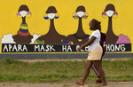 FILE — In this Thursday, Jan. 28, 2021 file photo, a woman walks past a coronavirus-themed mural promoting the use of face mask in public to protects against COVID-19 in Vereeniging, South Africa. A special unit in South Africa is investigating nearly $900 million worth of government procurement contracts related to the coronavirus pandemic for possible corruption. (AP Photo/Themba Hadebe, file)
