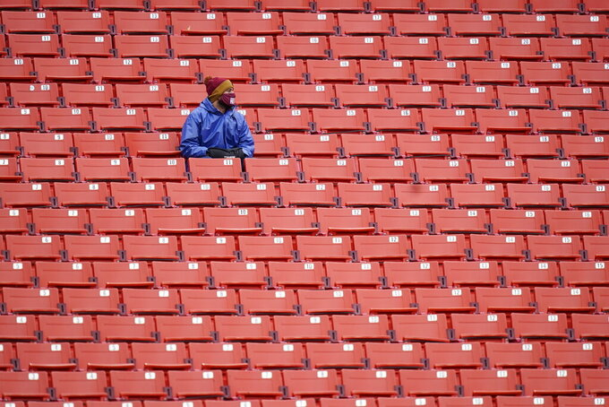 Fans sits in an empty seating section of Fedex Field during the first half of an NFL football game between Dallas Cowboys and Washington Football Team, Sunday, Oct. 25, 2020, in Landover, Md. (AP Photo/Patrick Semansky)