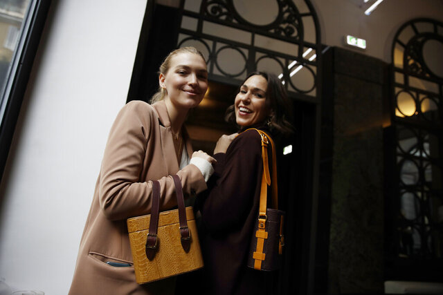 FILE - In this Feb. 24, 2019 file photo, model Arizona Muse, left, is flanked by designer and Officina del Poggio owner Allison Hoeltzel Savini as they present a creation of the Officina del Poggio women's Fall-Winter 2019-2020 collection, in Milan, Italy. The United States' fumbling response to the pandemic is casting doubt on its economic prospects and making it one of the chief risks that could undermine the rebound. Officina del Poggio sells 60% its vintage motorcycle-inspired satchels to U.S. customers. (AP Photo/Luca Bruno, file)