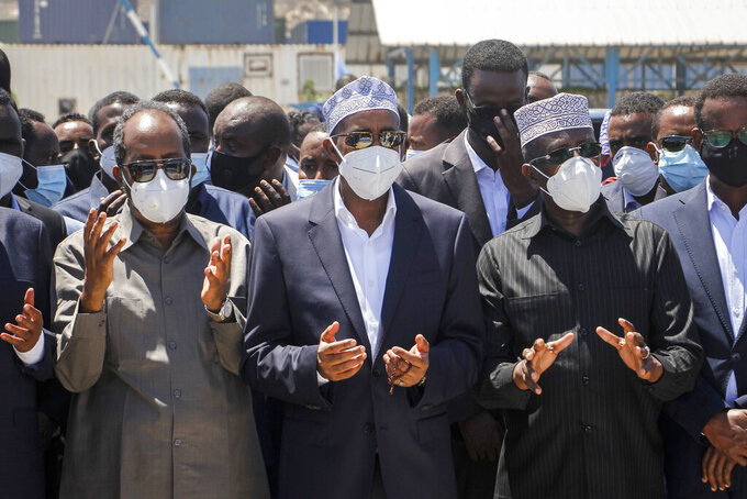 Former President Hassan Sheikh Mohamud, left, former Prime Minister Hassan Ali Khaire, center, and former President Sharif Sheikh Ahmed, right, pray over the body of former president Ali Mahdi Mohamed, who died of COVID-19 earlier this week in neighboring Kenya, at a state funeral held at the airport in Mogadishu, Somalia Friday, March 12, 2021. Somalia has declared three days of mourning during which the national flag will be lowered to half-staff in honor of the former president, who was 86. (AP Photo/Farah Abdi Warsameh)
