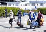 People arriving from Craiova in Romania walk past the police officers with their luggage and masks to a charter bus waiting at the 'Schoenefeld Airport' in Berlin, Germany, Thursday, April, 2020. The first planes with harvest workers from Romania have been landing in the morning. (Soeren Stache/dpa via AP)
