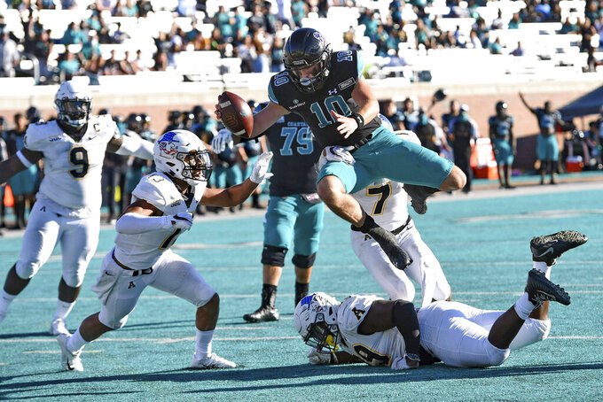 Coastal Carolina's Grayson McCall (10) runs on a quarterback keeper while defended by Appalachian State's Jordan Earle, bottom, and Trey Cobb (7) during the second half of an NCAA college football game Saturday, Nov. 21, 2020, in Conway, S.C. (AP Photo/Richard Shiro)