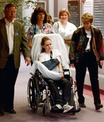 FILE - In this May 1, 1999, file photo, Kacey Ruegsegger, 17, is wheeled from a Denver hospital by Patty Anderson, center, after being released. Walking beside her are her parents Greg, left, and Darcy, right. Ruegsegger Johnson survived a shotgun blast during the 1999 shootings at Colorado's Columbine High School that left 12 students, one teacher, and both gunmen dead. (AP Photo/Ed Andrieski, File)