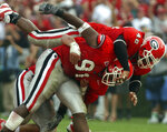 University of Georgia football players Shedrick Wynn (91) and Tony Gilbert (42) celebrate a sack against Tennessee during an NCAA college football game at Sanford Stadium in Athens, Ga., Saturday, Oct. 12, 2002. Wynn arrived at Georgia in 1999 to play football but never finished his college degree. Life kept getting in the way. Now, two decades later, he's finally got his cap and gown. (Jeff Blake/Athens Banner-Herald via AP)