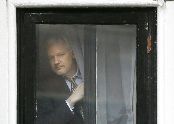 FILE - In this Friday, Feb. 5, 2016 file photo, Wikileaks founder Julian Assange appears at the window before speaking on the balcony of the Ecuadorean Embassy in London. A London court has heard that Julian Assange's conversations in the latter part of his seven-year stay at the Ecuadorian Embassy in London were systematically bugged, even in the toilet. Two anonymous witnesses who worked for a Spanish firm with a security contract at the embassy said the WikiLeaks founder faced an intensifying bugging operation after Donald Trump became U.S. president. (AP Photo/Kirsty Wigglesworth, File)