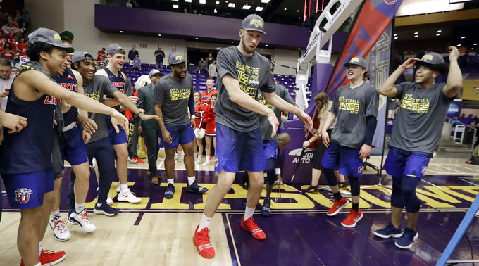 Liberty's Brendan Newton, center, dances as players celebrate after beating Lipscomb in the Atlantic Sun NCAA college basketball tournament championship game Sunday, March 10, 2019, in Nashville, Tenn. Liberty won 74-68. (AP Photo/Mark Humphrey)