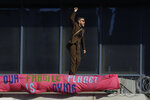 An Extinction Rebellion demonstrator gestures with a banner as he occupies a raised area at City Airport in London, Thursday, Oct. 10, 2019. Some hundreds of climate change activists are in London during a fourth day of world protests by the Extinction Rebellion movement to demand more urgent actions to counter global warming. (AP Photo/Matt Dunham)