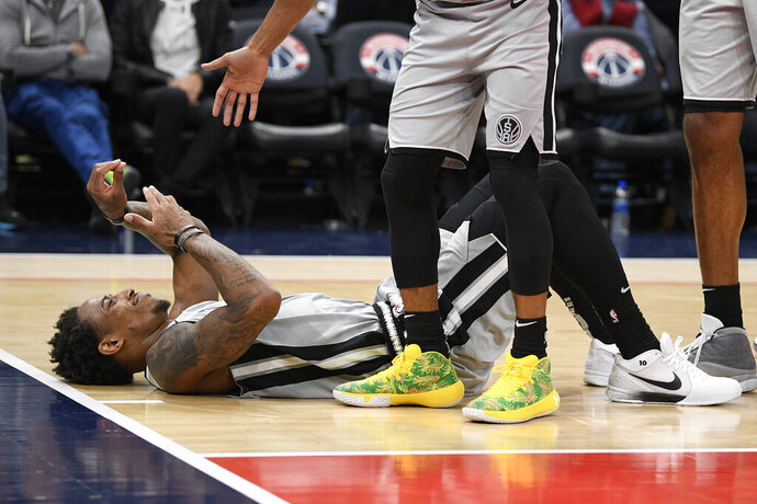 San Antonio Spurs guard DeMar DeRozan lies on the court after he was fouled during the second half of the team's NBA basketball game against the Washington Wizards, Wednesday, Nov. 20, 2019, in Washington. The Wizards won 138-132. (AP Photo/Nick Wass)