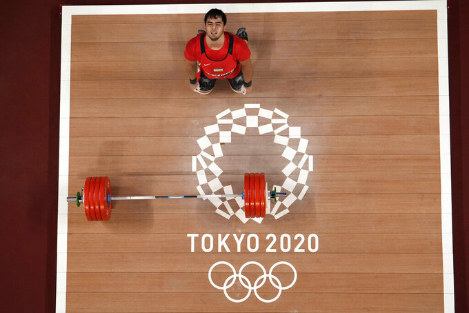 Akbar Djuraev of Uzbekistan celebrates after winning the gold medal and set a new olympic record in the men's 109kg weightlifting event, at the 2020 Summer Olympics, Tuesday, Aug. 3, 2021, in Tokyo, Japan. (AP Photo/Luca Bruno)