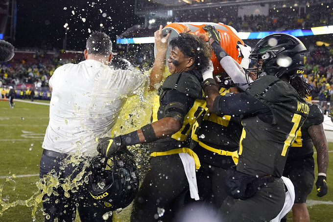Oregon players douse coach Mario Cristobal near the end of the team's 37-15 win over Utah in an NCAA college football game for the Pac-12 Conference championship in Santa Clara, Calif., Friday, Dec. 6, 2018. (AP Photo/Tony Avelar)
