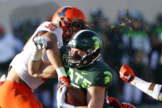 Michigan State tight end Matt Dotson is tackled by Illinois defensive back Sydney Brown (30) during the first half of an NCAA college football game, Saturday, Nov. 9, 2019, in East Lansing, Mich. (AP Photo/Carlos Osorio)