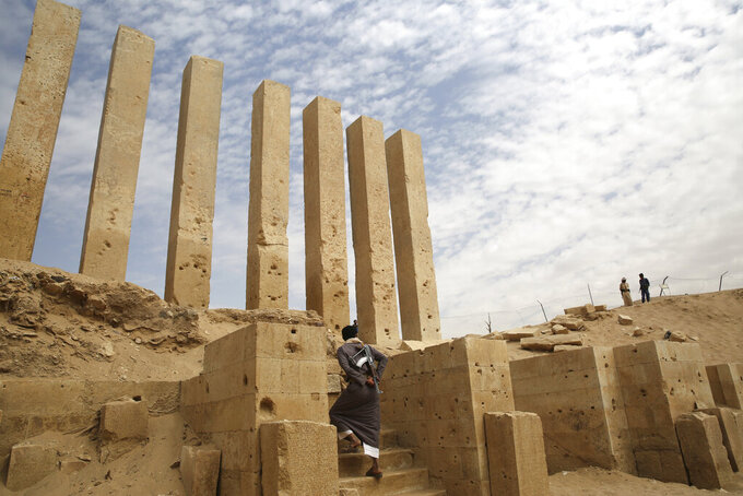 FILE - In this Feb. 3, 2018, file photo, a militiaman allied to Yemen's internationally recognized government walks through the Awwam Temple, also known as the Mahram Bilqis, in Marib, Yemen. The battle for the ancient desert city has become key to understanding wider tensions now inflaming the Middle East and the challenges facing any efforts by President Joe Biden's administration to shift U.S. troops out of the region.  (AP Photo/Jon Gambrell, File)