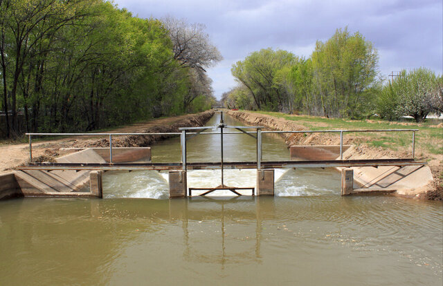 FILE - In this March 31, 2017, file photo, water flows through one of the irrigation canals in Albuquerque, N.M. New Mexico Gov. Michelle Lujan Grisham has long talked about the importance of water to the arid state, even campaigning on the idea of creating a 50-year plan to guide management of the finite resource. Her administration is now asking lawmakers for more money and manpower to start what some experts say will be a multiyear endeavor. (AP Photo/Susan Montoya Bryan, File)