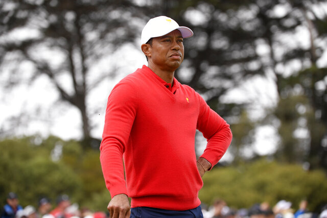 U.S. team player and captain Tiger Woods waits for International team player Abraham Ancer of Mexico to play a shot on the 1rst in their singles match during the President's Cup golf tournament at Royal Melbourne Golf Club in Melbourne, Sunday, Dec. 15, 2019. (AP Photo/Andy Brownbill)