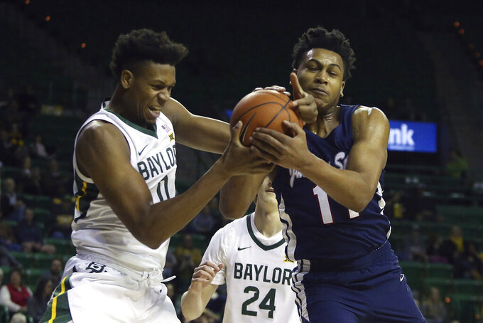 Baylor forward Flo Thamba (0) and Jackson State forward Jayveous McKinnis (11) battle for the ball in the first half of an NCAA college basketball game, Monday, Dec. 30, 2019, in Waco, Texas. (AP Photo/Jerry Larson)