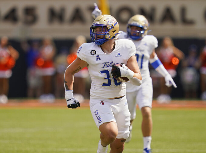 Tulsa linebacker Justin Wright (30) returns an interception for a touchdown in the first half of an NCAA college football game against Oklahoma State, Saturday, Sept. 11, 2021, in Stillwater, Okla. (AP Photo/Sue Ogrocki)
