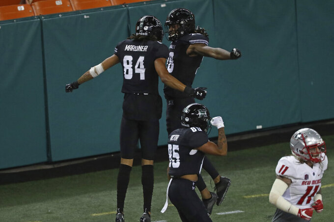 Hawaii wide receiver Nick Mardner (84) celebrates with wide receiver Aaron Cephus (28) after Mardner's touchdown against New Mexico during the second quarter of an NCAA college football game Saturday, Nov. 7, 2020, in Honolulu. (AP Photo/Marco Garcia)