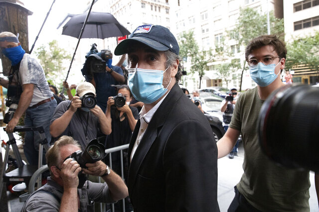 Michael Cohen, President Donald Trump's former personal attorney, returns to his apartment after being released from prison, Friday, July 24, 2020, in New York. District Judge Alvin Hellerstein ordered Cohen released on parole saying he believes the government retaliated against him for writing a book about Trump. (AP Photo/Mark Lennihan)