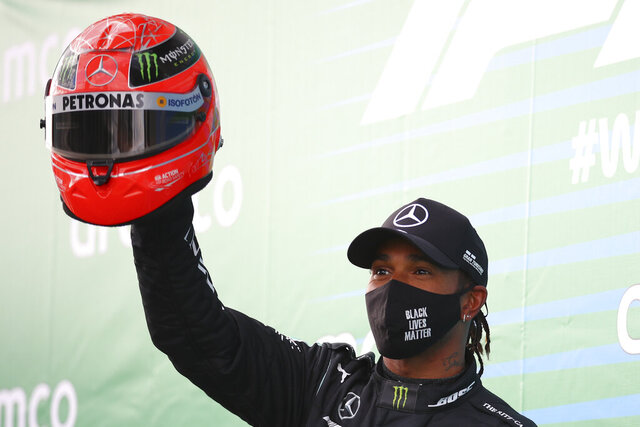 Mercedes driver Lewis Hamilton of Britain shows a helmet of former German driver Michael Schumacher after he wins the Eifel Formula One Grand Prix at the Nuerburgring racetrack in Nuerburg, Germany, Sunday, Oct. 11, 2020. Hamilton gets the helmet as a gift from Michael Schumacher's son Mick because he equals Schumacher's record of 91 wins in the Formula One. (Bryn Lennon, Pool via AP)