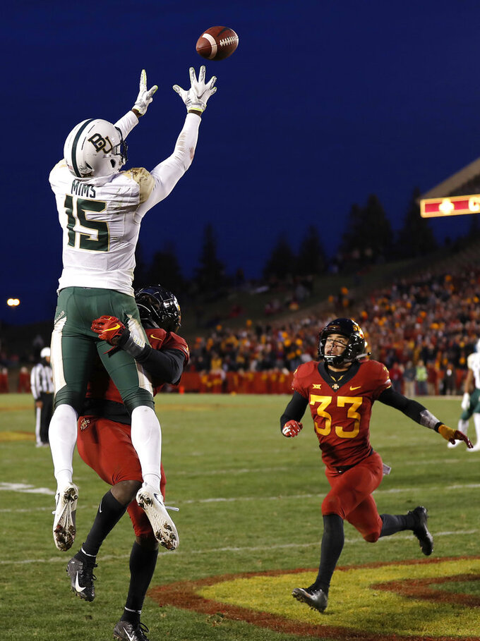Baylor wide receiver Denzel Mims (15) pulls in a reception for a touchdown despite defensive efforts by Iowa State defensive back Brian Peavy, back left, during the second half of an NCAA college football game, Saturday, Nov. 10, 2018, in Ames. (AP Photo/Matthew Putney)