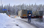 A truck driver with customs clearance documents walks towards the Norwegian Customs office at the Orje border crossing between Sweden and Norway, on Friday, Feb. 8 2019. Norway's hard border with the European Union is equipped with cameras, license-plate recognition systems and barriers directing traffic to Customs officers. Norway's membership in the European Economic Area (EEA) grants it access to the common market and most goods are exempt from paying duties but everything entering the country must be declared and cleared through customs. (AP Photo/David Keyton)