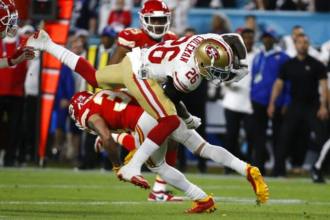 San Francisco 49ers' Tevin Coleman (26) runs against Kansas City Chiefs' Tyrann Mathieu (32) during the first half of the NFL Super Bowl 54 football game Sunday, Feb. 2, 2020, in Miami Gardens, Fla. (AP Photo/Mark Humphrey)