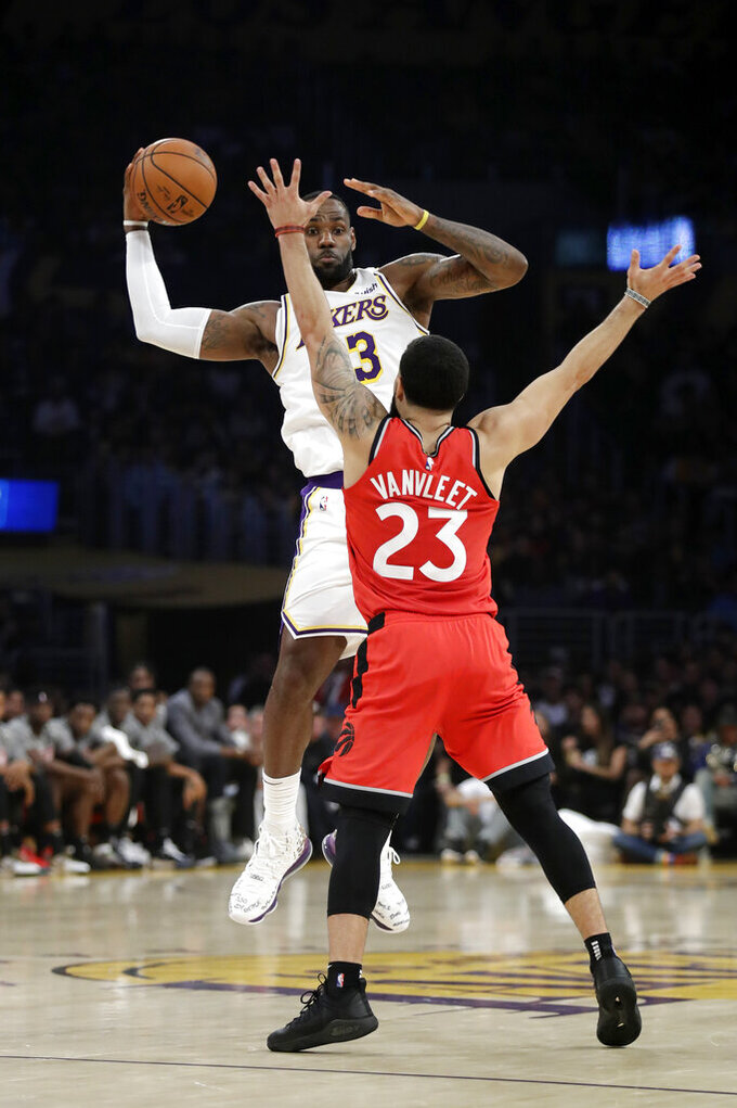 Los Angeles Lakers' LeBron James, rear, is defended by Toronto Raptors' Fred VanVleet during the first half of an NBA basketball game Sunday, Nov. 10, 2019, in Los Angeles. (AP Photo/Marcio Jose Sanchez)