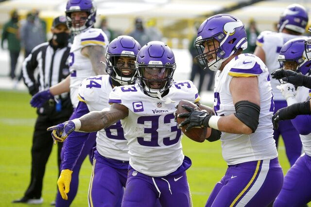 Minnesota Vikings' Ezra Cleveland (72) helps Dalvin Cook (33) celebrate his touchdown run during the second half of an NFL football game against the Green Bay Packers Sunday, Nov. 1, 2020, in Green Bay, Wis. (AP Photo/Mike Roemer)