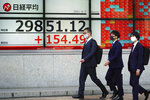 Men wearing protective masks walk in front of an electronic stock board showing Japan's Nikkei 225 index at a securities firm Wednesday, April 7, 2021, in Tokyo. Asian shares were mixed Wednesday after Wall Street took a breather, with major indexes edging lower. (AP Photo/Eugene Hoshiko)