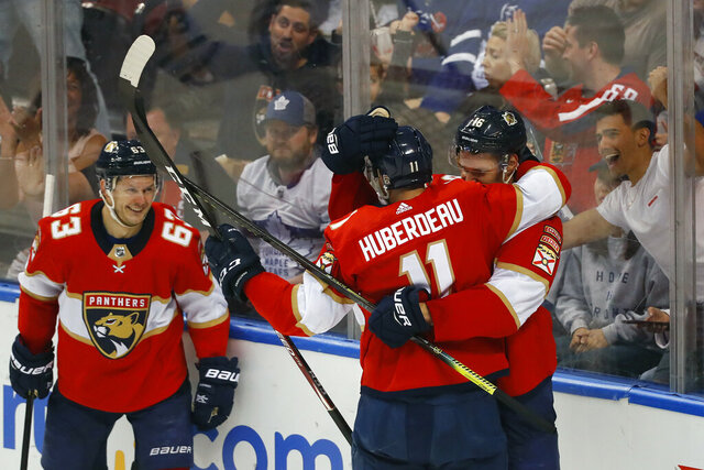 Florida Panthers left wing Jonathan Huberdeau (11) is congratulated by center Aleksander Barkov (16) and right wing Evgenii Dadonov (63) after he scored a goal during the second period of an NHL hockey game against the Toronto Maple Leafs, Sunday, Jan. 12, 2020, in Sunrise, Fla. (AP Photo/Wilfredo Lee)