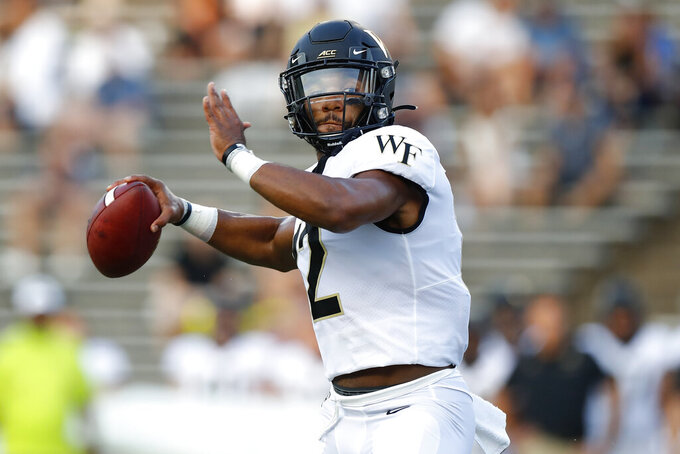 FILE - In this Sept. 6, 2019, file photo, then-Wake Forest quarterback Jamie Newman (12) looks to pass during an NCAA football game in Houston. Two transfers, Jamie Newman, from Wake Forest, and JT Daniels, from Southern Cal, are names to watch in Georgia's five-player quarterback competition. Newman may be the favorite as practice started Monday because Daniels is still recovering from a knee injury at USC. (AP Photo/Matt Patterson, File)