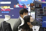 Currency traders watch monitors at the foreign exchange dealing room of a KB Kookmin Bank branch in Seoul, South Korea, Thursday, Jan. 14, 2021. Shares were mostly higher in Asia on Thursday after a lackluster day on Wall Street, where major indexes spent the day drifting up and down near their record highs. (AP Photo/Ahn Young-joon)