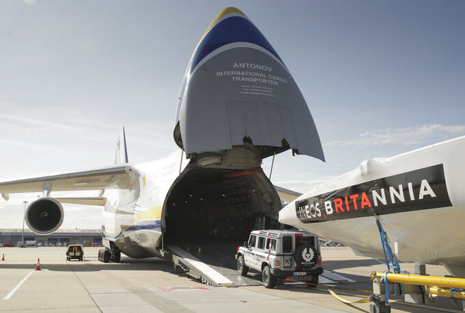 This Sept. 28, 2020  photo provided by INEOS Team UK shows the INEOS TEAM UK America's Cup race boat being towed onto an Antonov cargo plane by the teams new prototype INEOS 'Grenadier' 4x4 at the start of its journey to Auckland, New Zealand, at London Stansted Airport in England. England's never-ending quest to win back the America's Cup it lost so long ago is taking another step forward with the team's relocation to New Zealand for sailing's marquee regatta. (Mark Lloyd Images/INEOS Team UK via AP)