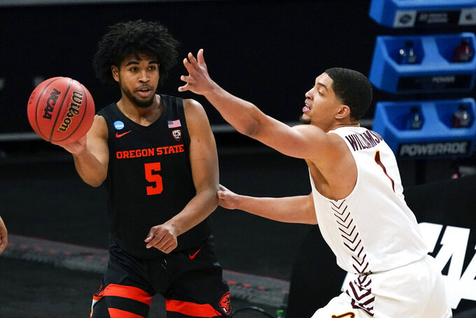 Oregon State guard Ethan Thompson (5) passes around Loyola Chicago guard Lucas Williamson (1) during the first half of a Sweet 16 game in the NCAA men's college basketball tournament at Bankers Life Fieldhouse, Saturday, March 27, 2021, in Indianapolis. (AP Photo/Jeff Roberson)