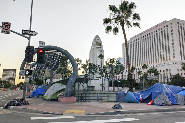 FILE - This March 28, 2020, file photo shows homeless people camping in downtown in Los Angeles. A $1.2 billion program aimed at building housing for homeless people in Los Angeles has been plagued by delays and soaring costs that have seen the average price of constructing a single unit jump to nearly $559,000, according to a city audit, on Wednesday, Sept. 9. (AP Photo/Damian Dovarganes, File)