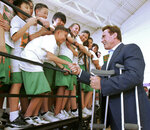 FILE - In this Jan. 24, 2007 file photo, eighth grader Tou Her, center, 13, squeezes between schoolmates to shake hands with California Gov. Arnold Schwarzenegger, right, who visited Will C. Wood Middle School in Sacramento, Calif., Wednesday, Jan. 24, 2007. As part of his effort to boost students' physical fitness, Schwarzenegger had announced a fitness challenge. Current California Gov. Gavin Newsom wants a three-year suspension on physical fitness tests while the state studies whether the current test for children in fifth, seventh and ninth grades can be modified or a new assessment should be drawn up. (AP Photo/Rich Pedroncelli, File)