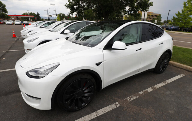 FILE - In this Sunday, June 28, 2020 file photo, 2020 Model Y electric sports-utility vehicles sit in the parking lot of a Tesla store in Littleton, Colo. Tesla overcame a seven-week pandemic-related shutdown at its U.S. assembly plant to post a $104 million net profit for the second quarter. (AP Photo/David Zalubowski)