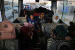 Syrians who are newly displaced by the Turkish military operation in northeastern Syria, sit in a bus upon their arrival at the Bardarash camp, north of Mosul, Iraq, Wednesday, Oct. 16, 2019. The camp used to host Iraqis displaced from Mosul during the fight against the Islamic State group and was closed two years ago. The U.N. says more around 160,000 Syrians have been displaced since the Turkish operation started last week, most of them internally in Syria. (AP Photo/Hussein Malla)