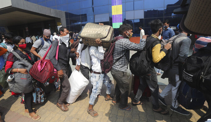People wearing masks as a precaution against the coronavirus stand in queues to board trains at Lokmanya Tilak Terminus in Mumbai, India, Wednesday, April 14, 2021. India is experiencing its worst pandemic surge, with average daily infections exceeding 143,000 over the past week. (AP Photo/Rafiq Maqbool)