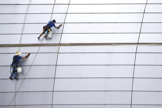 FILE - In this July 31, 2019, file photo workers clean the outside facade of State Farm Stadium in Glendale, Ariz. On Wednesday, Oct. 16, the Federal Reserve releases its latest 'Beige Book' survey of economic conditions. (AP Photo/Ross D. Franklin)