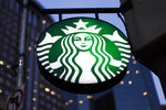 "FILE - This June 26, 2019 file photo shows a the Starbucks sign outside a Starbucks coffee shop in downtown Pittsburgh.  A Starbucks employee wrote ""PIG"" on a Thanksgiving Day 2019 order placed in person by a police officer in Kiefer, Okla.  A claim circulated on Twitter suggested that police submitted pig as the name on the order to draw sympathy. According to a joint statement issued by Starbucks and Kiefer police, it was a store employee who wrote ""PIG"" on the cups. The company said in a Nov. 29, 2019 statement that the employee who wrote the ""offensive word on a cup"" exercised poor judgment and was no longer a Starbucks employee after violating company policy.T (AP Photo/Gene J. Puskar)"