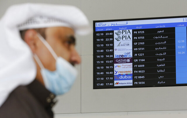 A Saudi waits for the arrival of relatives from Qatar in front of a screen displaying a Qatar Airways flight for the first time in 3 years, at King Khalid Airport in Ryadh, Saudi Arabia, Monday, Jan. 11, 2021. Saudi Arabia, along with the UAE, Bahrain and Egypt, ended a three-year dispute with Qatar following a Gulf Cooperation Council (GCC) summit in AlUla last week. (AP Photo/Amr Nabil)