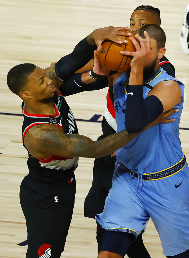 Portland Trail Blazers' Damian Lillard, left,and Memphis Grizzlies' Jonas Valanciunas tangle during the second half of an NBA basketball game Saturday, Aug. 15, 2020, in Lake Buena Vista, Fla. (Kevin C. Cox/Pool Photo via AP)