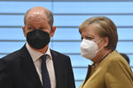 German Chancellor Angela Merkel, right, talks with German Finance Minister and Vice-Chancellor Olaf Scholz prior to the weekly cabinet meeting at the Chancellery in Berlin, Germany, Tuesday April 13, 2021. (John MacDougall/AP via Pool)