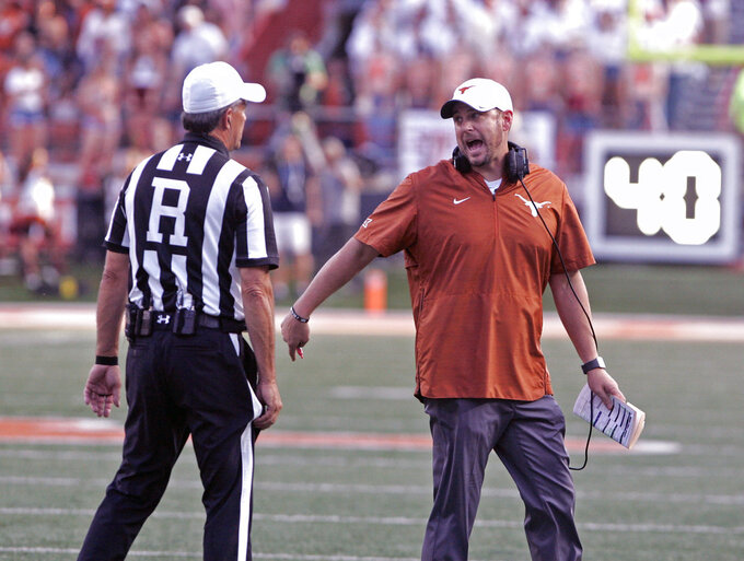 Texas head coach Tom Herman talks with the referee during the second half of an NCAA college football game against West Virginia, Saturday, Nov. 3, 2018, in Austin, Texas. West Virginia won 42-41. (AP Photo/Michael Thomas)